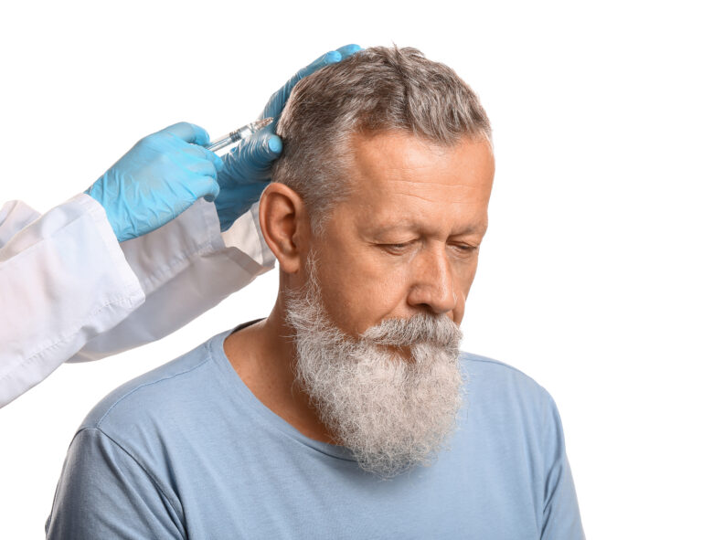 Senior man with hair loss problem receiving injection on white background