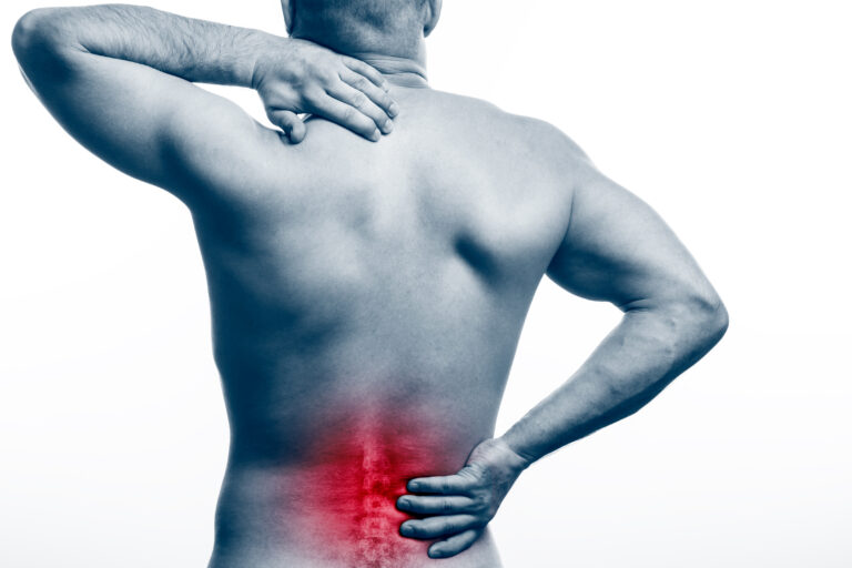 Pain in the spine.  Young bald man sports physique holds a sick back on a white isolated background. Fracture of spine